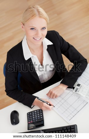 Cheerful accountant businesswoman working in the office - stock photo