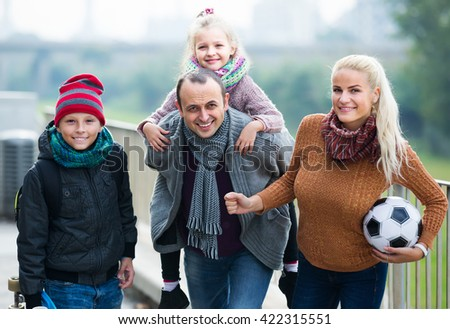 Cheerful active parents with two smiling children spending time together outdoors - stock photo