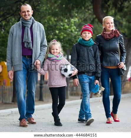 Cheerful active parents with two smiling children spending weekend together outdoors - stock photo