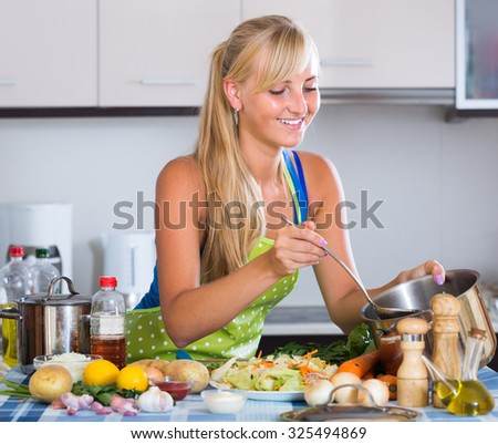 Cheerful adult  blondie preparing veggies in domestic kitchen  - stock photo