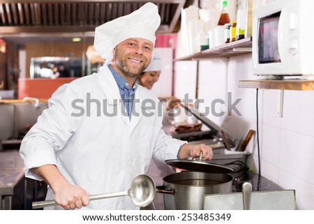 Cheerful adult cooks cooking at professional kitchen in the take-away  restaurant - stock photo