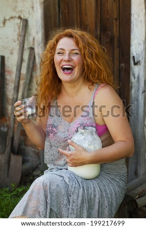 cheerful adult woman lead healthy lifestyle drinking milk in the village outside - stock photo