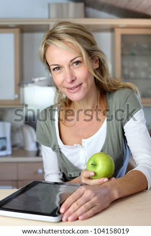 Cheerful adult woman websurfing with tablet and eating apple - stock photo