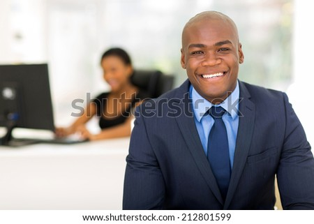 cheerful african american businessman in office with colleague on background - stock photo