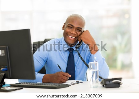 cheerful african american businessman talking on phone in the office - stock photo