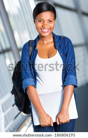 cheerful african american college student with laptop computer on campus - stock photo