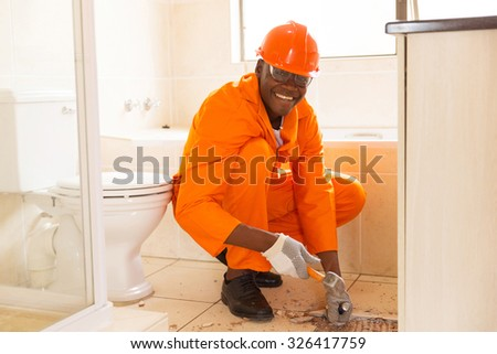 cheerful african american construction worker removing floor tiles in bathroom - stock photo