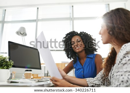 Cheerful African-American female entrepreneur listening to her colleague - stock photo