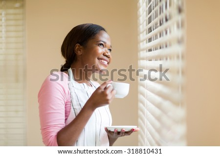 cheerful african american housewife having coffee at home - stock photo