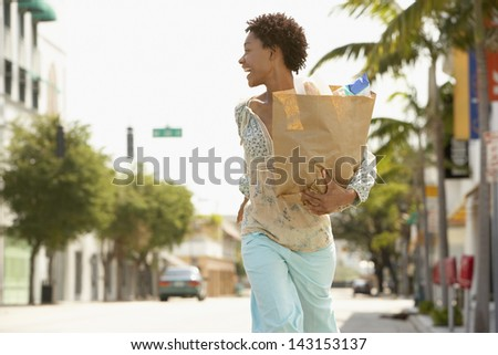 Cheerful African American woman carrying grocery bag while walking on street