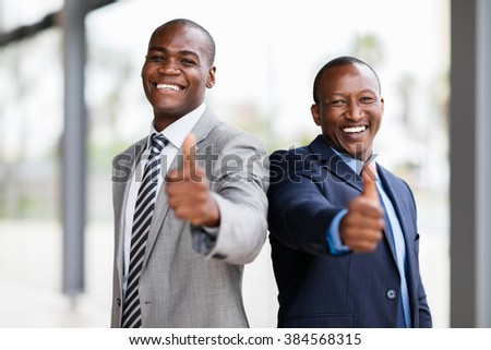 cheerful african business team giving thumbs up - stock photo