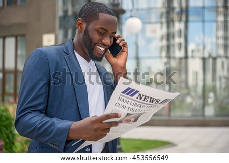 Cheerful African businessman with telephone and newspaper