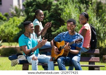 cheerful african college boy playing guitar for friends - stock photo