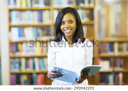 cheerful african college student reading a book in library - stock photo