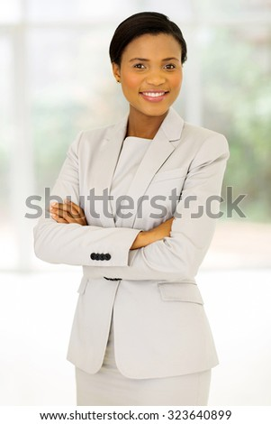 cheerful african entrepreneur with arms crossed in office