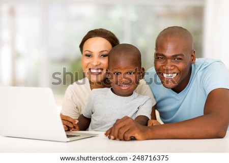 cheerful african family with laptop computer