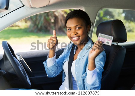 cheerful african girl holding her driver's license she just got - stock photo