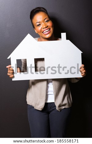 cheerful african girl holding paper house on black background - stock photo