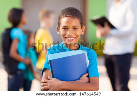 cheerful african male elementary school student holding text books - stock photo