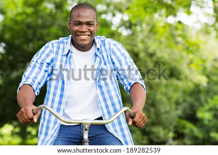 cheerful african man having fun riding a bicycle in forest - stock photo