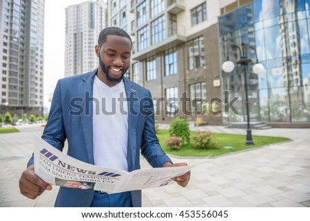 Cheerful African man is interested in news - stock photo