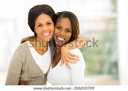 cheerful african mother and daughter hugging at home - stock photo