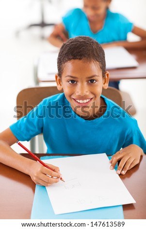cheerful african schoolboy writing classwork in classroom - stock photo