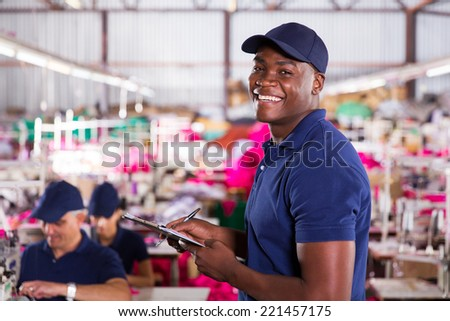 cheerful african textile factory worker in production area - stock photo