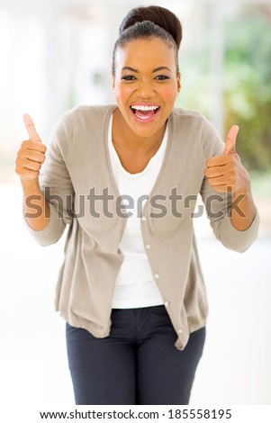 cheerful african woman giving two thumbs up as sign of approval - stock photo