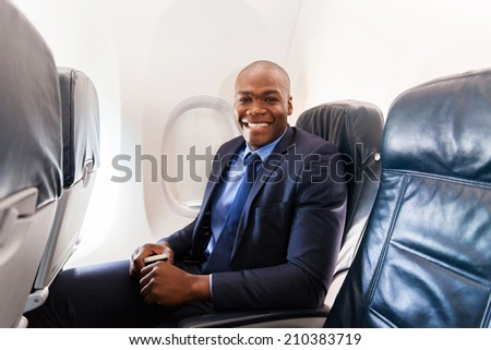 cheerful afro american businessman on board of an airplane during the flight - stock photo