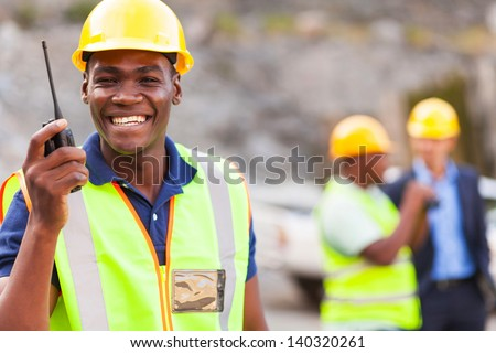 cheerful afro american mine worker with walkie talkie - stock photo