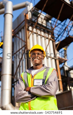 cheerful afro american oil industrial worker with arms crossed in refinery plant - stock photo