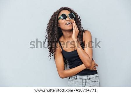 Cheerful afro american woman in glasses posing over gray background - stock photo