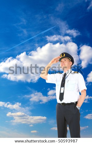 Cheerful airline pilot wearing uniform with epaulets and hat looking upwards, standing over a beautiful blue cloudy sky with flying jet airplane. - stock photo