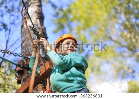 cheerful and brave boy at a height. child enjoys the view from the top in the ropes course and prepare for extreme downhill - stock photo