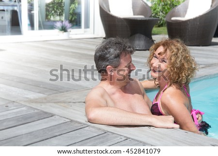 Cheerful and charming couple having fun in swimming-pool - stock photo