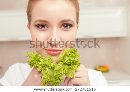 Cheerful and fresh. Beautiful fair-haired woman being pleased with color, smell and taste of lettuce leafs holds them in her hands and shows it to you smiling  - stock photo