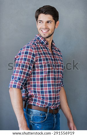 Cheerful and handsome. Smiling young man looking over shoulder while standing against grey background - stock photo