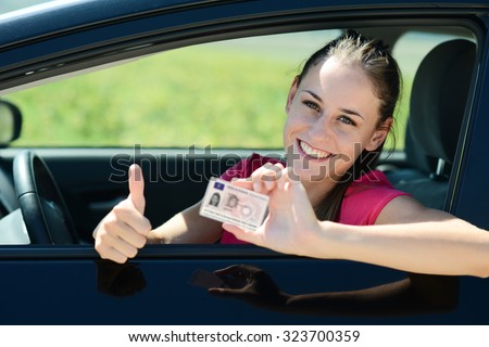cheerful and happy young woman in her car showing her new driving license - stock photo