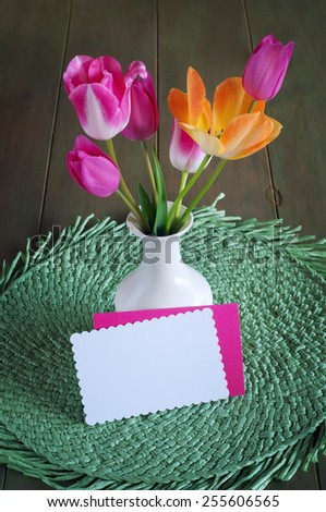 Cheerful and Pretty Orange and Pink Spring Tulips in a White Vase on a  Wood Table and green placemat with Notecard, blank for your words, text, copy.  Vertical looking down from above view, - stock photo