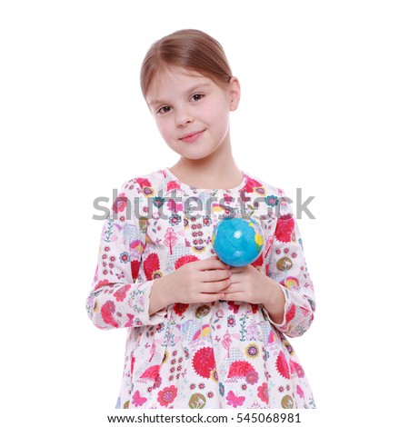 Cheerful and smiling little girl holding and offering globe