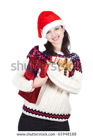 Cheerful and smiling woman in red Santa hat is keeping boxes with gifts - stock photo