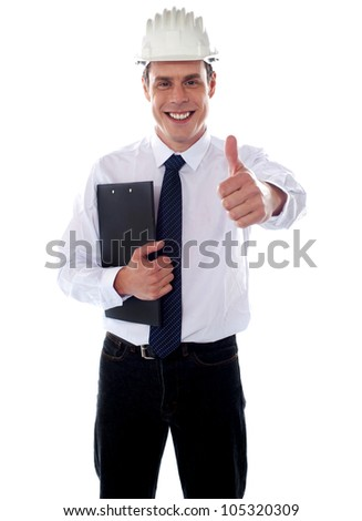 Cheerful architect gesturing thumbs up wearing hard hat and holding clipboard - stock photo