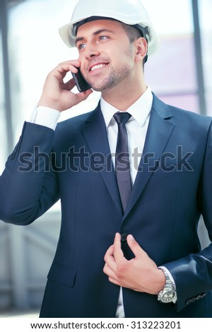 Cheerful architect is communication with his customer by telephone. He is standing and smiling. The man is buttoning his suit. He is wearing a white helmet - stock photo