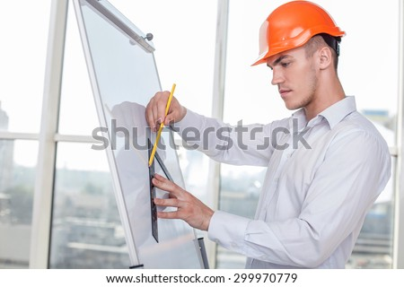 Cheerful architect is drawing sketches of building with a ruler and pencil. He is doing it on a vertical board with inspirations - stock photo