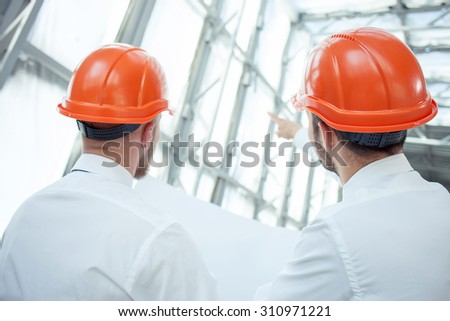 Cheerful architect is explaining to foreman the concepts of building new construction. He is pointing his index finger forward. The men are looking there with concentration. Focus on their back - stock photo