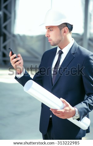 Cheerful architect is holding a mobile phone and messaging to his customer. He is looking at the screen seriously. The man is standing and holding a blueprint - stock photo