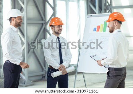 Cheerful architect is showing to his team the results of their work. His colleagues are looking at the blueprint and smiling happily - stock photo
