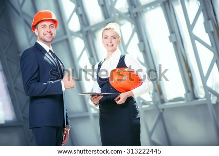 Cheerful architects are planning new project. They are standing and smiling. The man in helmet is giving thumb up. The blond woman is holding a folder of documents and looking forward happily - stock photo
