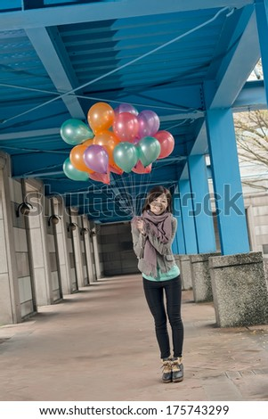 Cheerful Asian beauty holding balloons under bridge in city. - stock photo